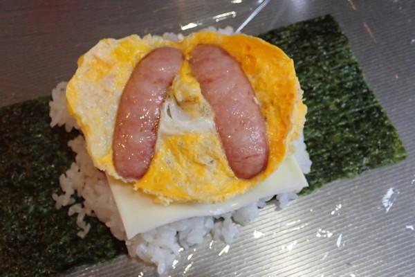 SiSO-LAB☆増量おにぎらず、海苔1枚で大きく作ってみるよ。卵とウィンナーを乗せるよ。